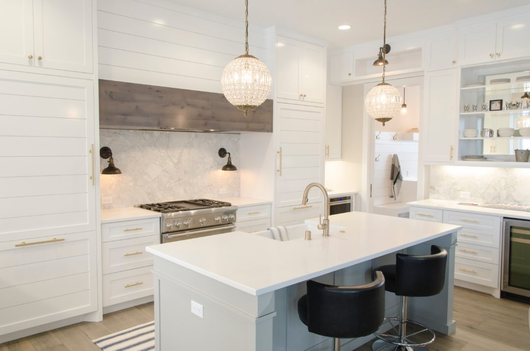 white kitchen with light wood floor, pendant lights, two bar stools